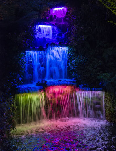 View of illuminated waterfall in forest