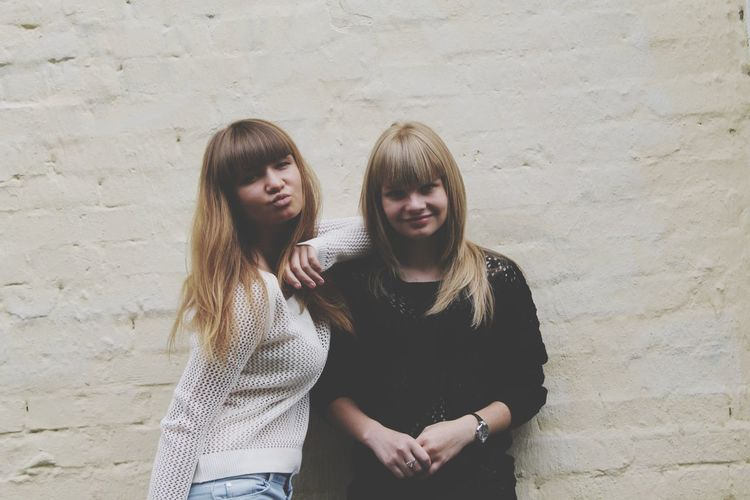 Portrait of young women smiling while standing against wall
