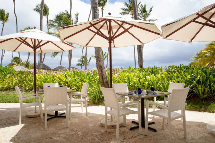Empty chairs and tables at beach against clear sky