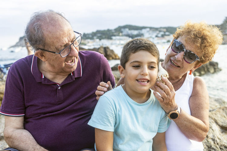Grandparents and grandson playing with a toy sailboat on the beach