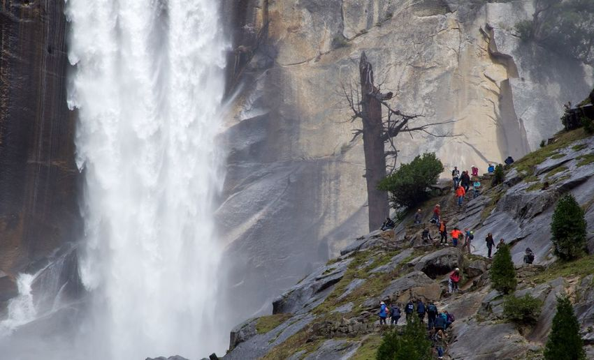 Hikers walking on mountain against vernal fall