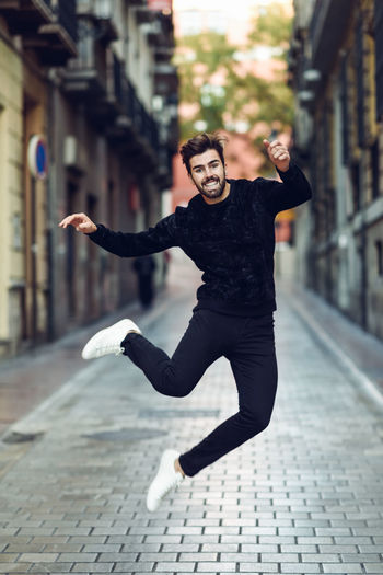 Portrait of smiling man jumping over road in city