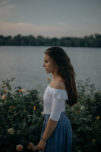 Side view of thoughtful young woman standing by plants against lake