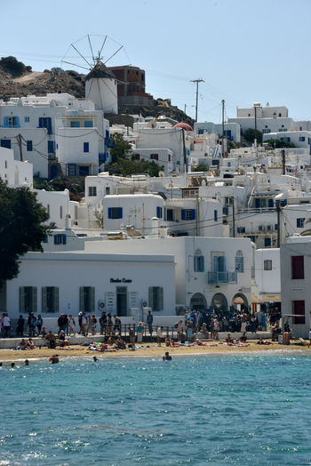 panoramic seaside view of Mykonos with white buildings and a beach full of people Building Exterior Architecture Water Built Structure Crowd Building Real People Sea Nature Sky Waterfront Residential District Large Group Of People Day Group Of People City Trip Travel Destinations Vacations Outdoors Seaside Beach Leisure Activity Mykonos,Greece Chora Greek Architecture Summertime Relaxing Windmill Holiday
