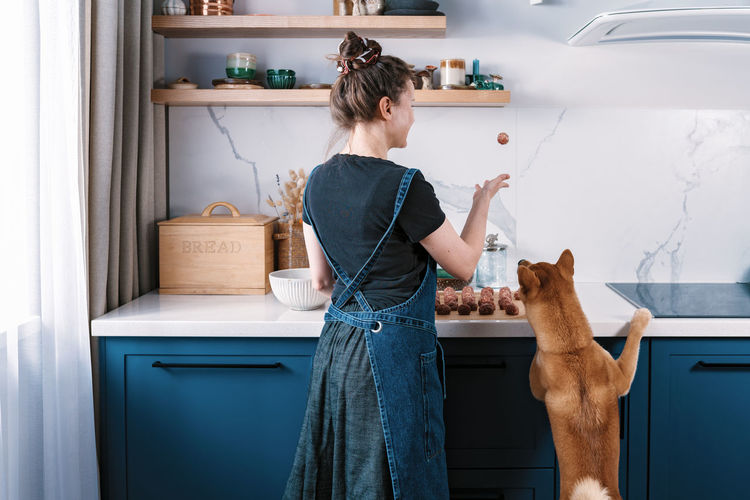 Funny woman cooking meatballs with her furry friend shiba inu dog. cooking at home