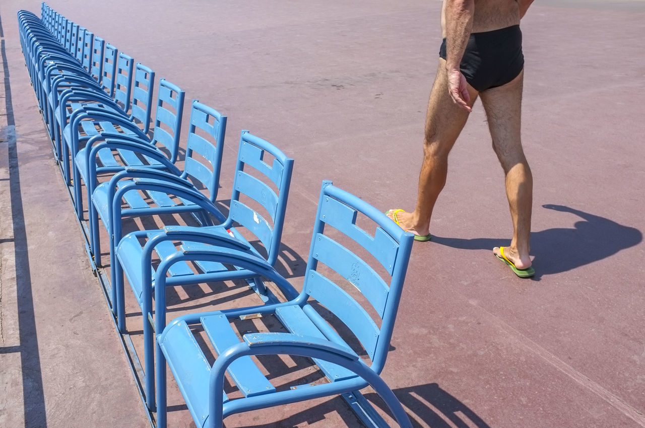 Low section of man walking by blue chairs