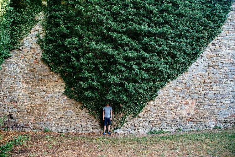 Man Standing On Field Against Creeper Plants On Old Wall