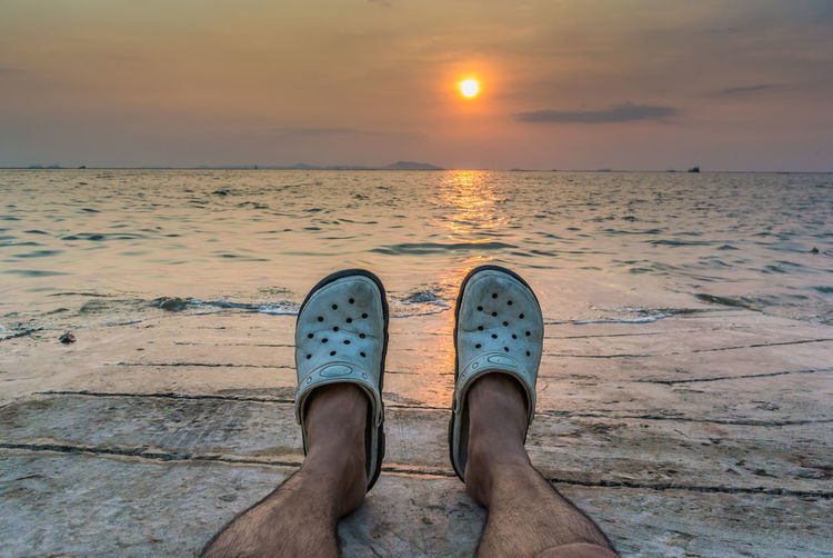 My feet with sunset sky at sea background Beach Beauty In Nature Cloud - Sky Day Horizon Over Water Human Body Part Human Leg Lifestyles Low Section Men Nature One Person Orange Color Outdoors People Personal Perspective Real People Sand Scenics Sea Shoe Sky Sunset Water