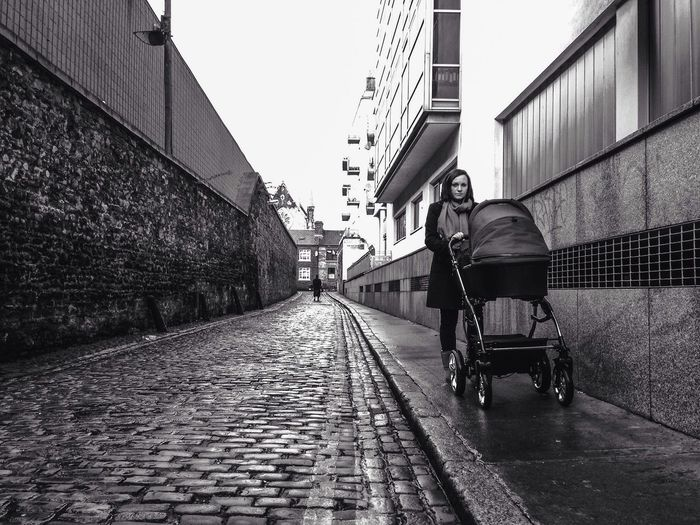 Woman With Baby Carriage Walking In Alley At City