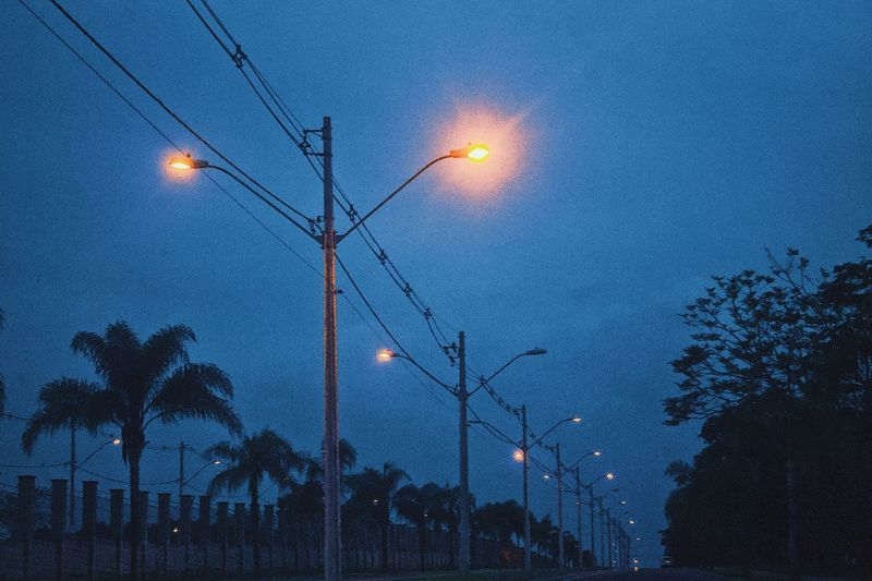 Low angle view of street lights against sky at night