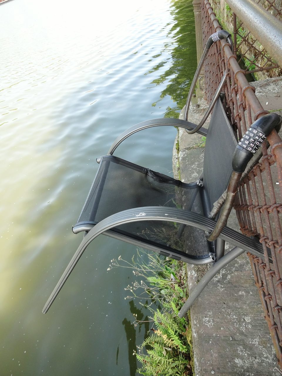 High Angle View Of Chair On Fence By Lake