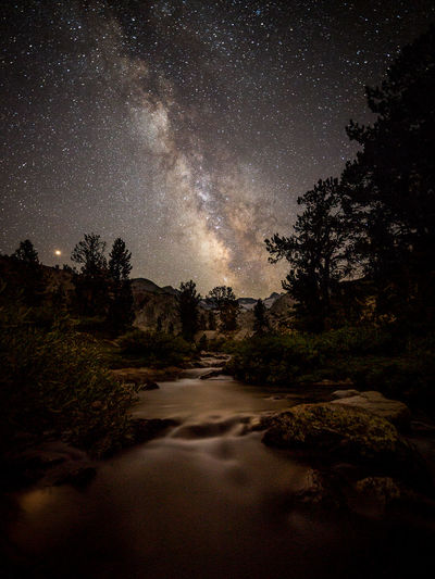 First night on John Muir Trail JMT DAY 1 - MILKY WAY OVER MT. LYELL AND FORK BELOW DONOHUE PASS Tuolumne Meadows to first lake below Donohue Pass: JMT201801002 Night fell at the first lake below Donohue Pass. Contrary to my worry that the night sky would be quite hazy by the smoke from the Ferguson Fire, the heavenly body stayed clear and the stars shone bright. Of course, the Milky Way was going to be erected quite vertically by the time when it was dark enough for it to be seen since it was already early August. The upside of it was that I didn't have to wait too long to capture the galactic core fully seen even though it wasn't late. For instance, it was already clearly visible at around 9:45 pm PST, as opposed to close to midnight if it were some time in June. The downside of it of course was that the duration of the galaxy traversing the night sky was a whole lot shorter. In fact, it was pretty much half the duration, compared to some time in June. I knew that me being near the outlet of the lake would not let me be able to frame Mt. Lyell and its adjacent peaks AND the Milky Way together when it rose. So, I had scouted father down Lyell Fork and found a spot that I could work with. Once it was dark, I returned to the spot and composed my shot. It had been a long day. I didn't even eat dinner till I was done with the sunset shots. And when I did, I chowed it down fast so that I could be ready for astrophotography. Did I already mention that I had been lugging a 70 plus lb backpack during the day? The camera gear alone weighed 30 lb. I was physically exhausted. But I wanted to make the whole experience of being out there worthwhile. And I was truly a happy camper capturing the beautiful moments on the first night on the John Muir Trail. Donohue Pass, Yosemite National Park, CA Donohue Pass Galaxy Lyell Fork Yosemite National Park Adventure Astronomy Astrophotography Beauty In Nature Forest Long Exposure Milky Way Nature Night Night Sky No People Non-urban Scene 