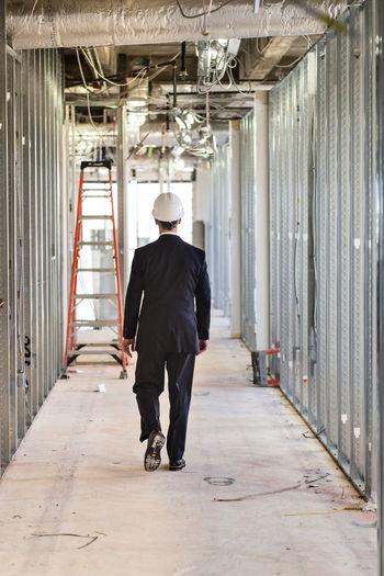 Rear view of engineer walking in corridor
