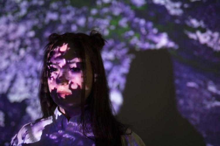 Portrait of woman looking at purple flower