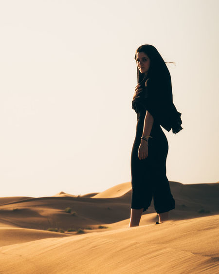 Full length of woman standing against clear sky during sunset