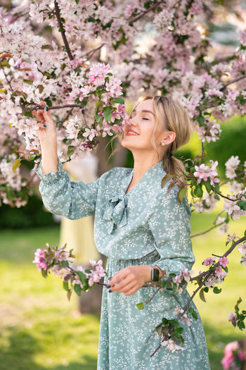 Woman standing by flower tree