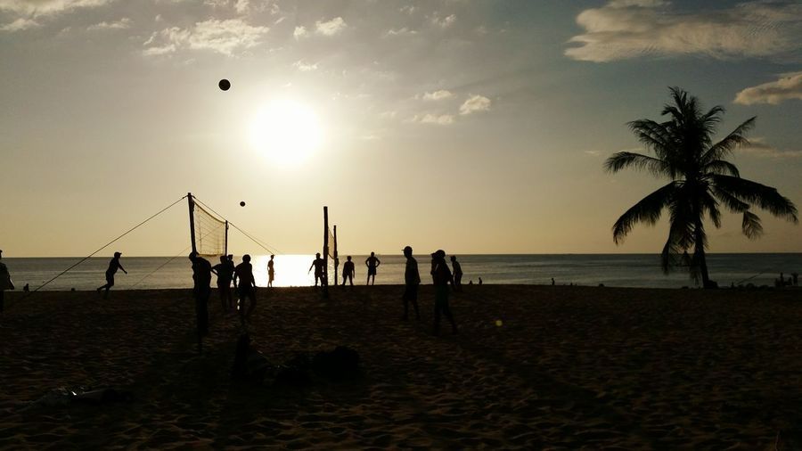 Silhouette people playing volleyball at beach against sky during sunset