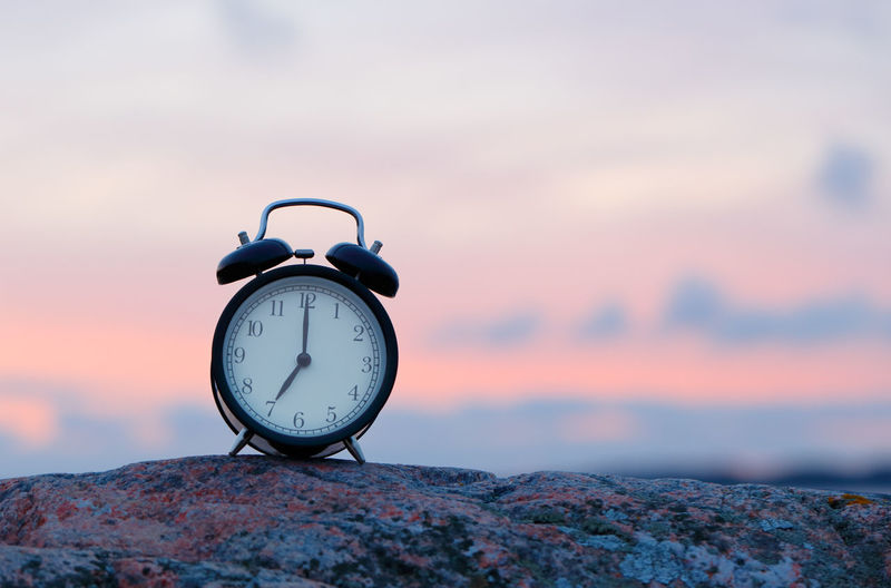 One black alarm clock on rock at seven o clock outdoor during sunrise. 7 7 O'clock Morning Alarm Clock Clock Clock Face Evening Focus On Foreground Hour Hand Minute Hand Nature No People Outdoors Seven O'clock Sky Sunset Time