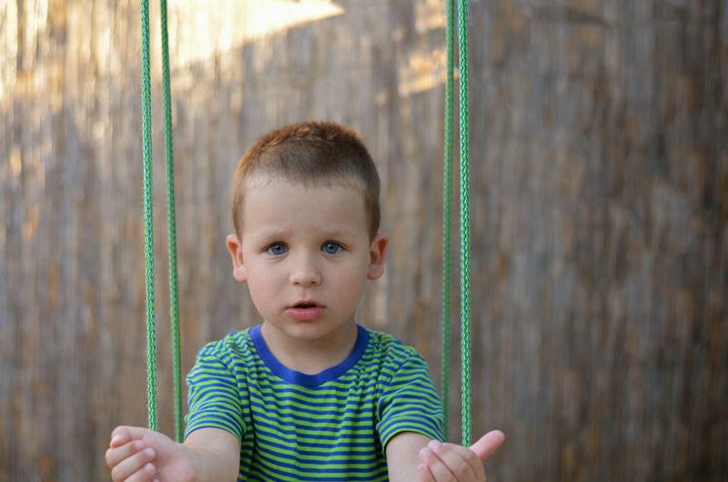 Close-up of boy on swing