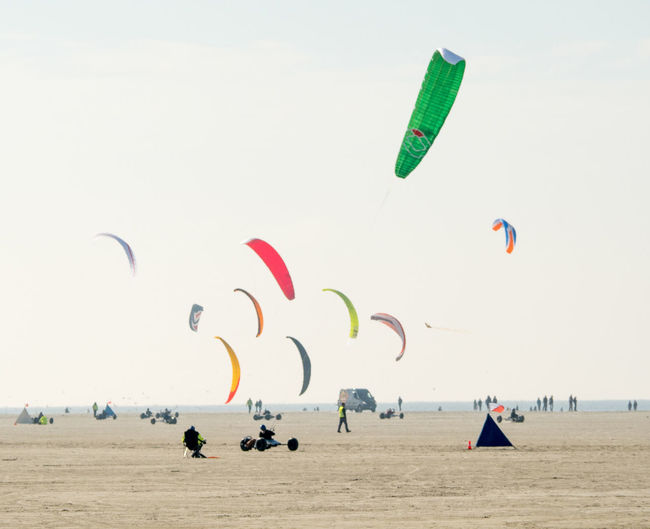 Multi colored parachutes fling over beach against clear sky