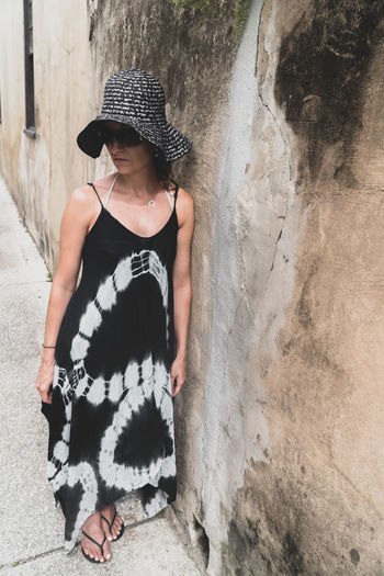 Woman wearing hat and looking away while standing against wall