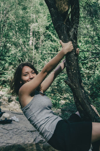 Portrait of woman hanging on tree trunk