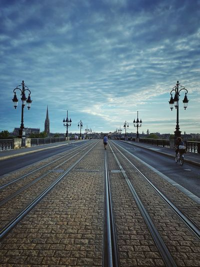 Railroad tracks by street against sky