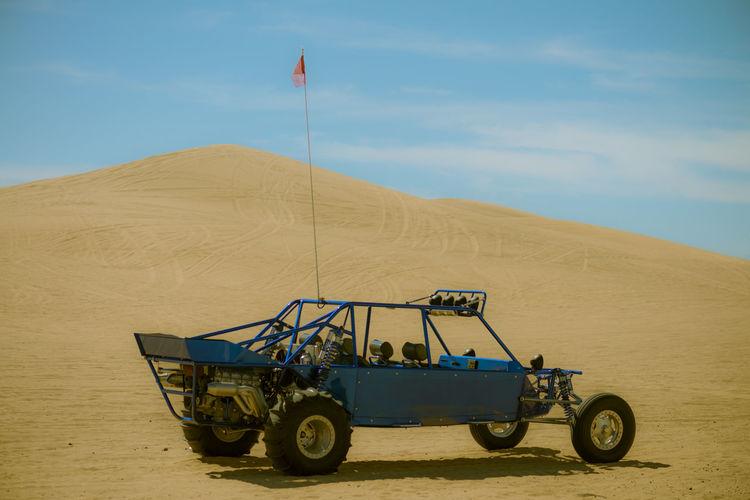 Off-Road Vehicle In Desert Against Sky