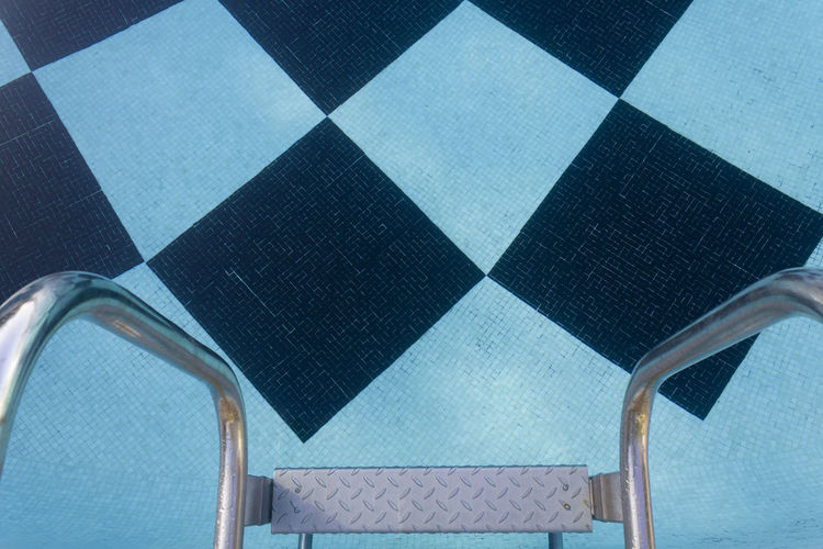 Low angle view of tiled floor against blue sky
