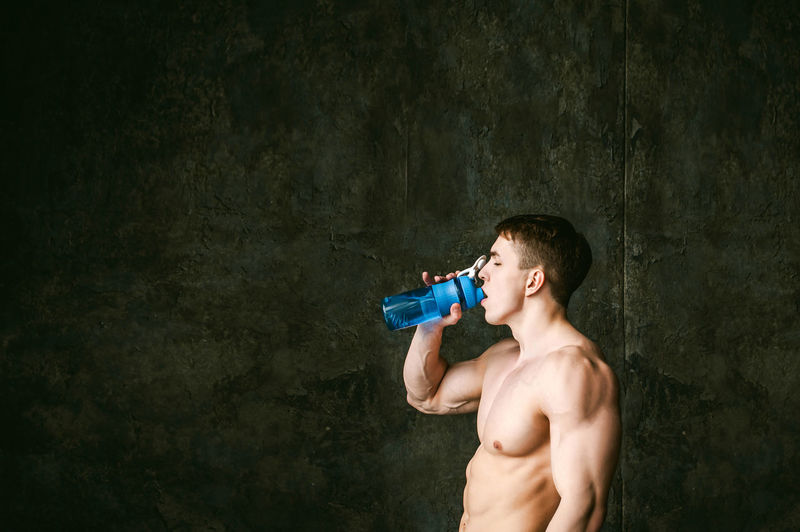 Shirtless Man Drinking While Gesturing Thumbs Up By Wall
