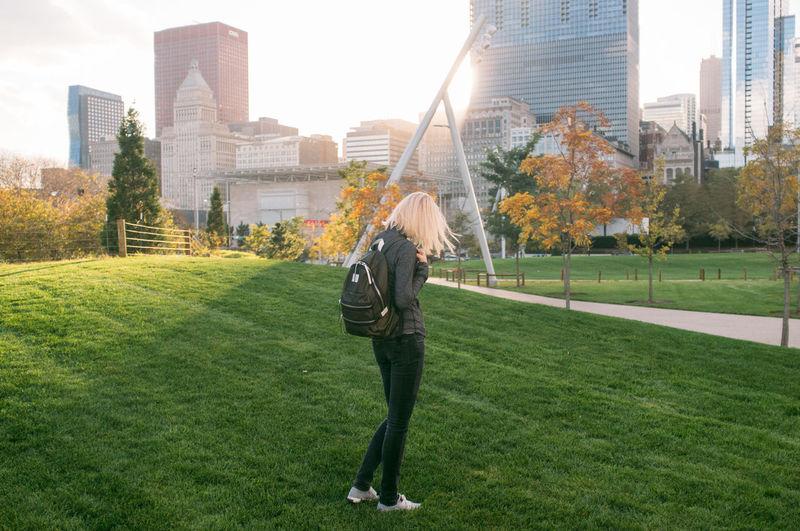 Woman at millennium park against modern buildings in city