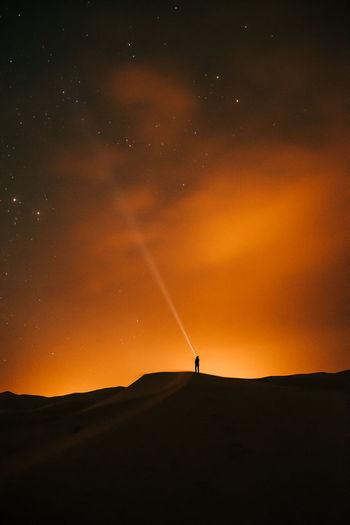 Silhouette person on land against sky during sunset in the desert full of stars