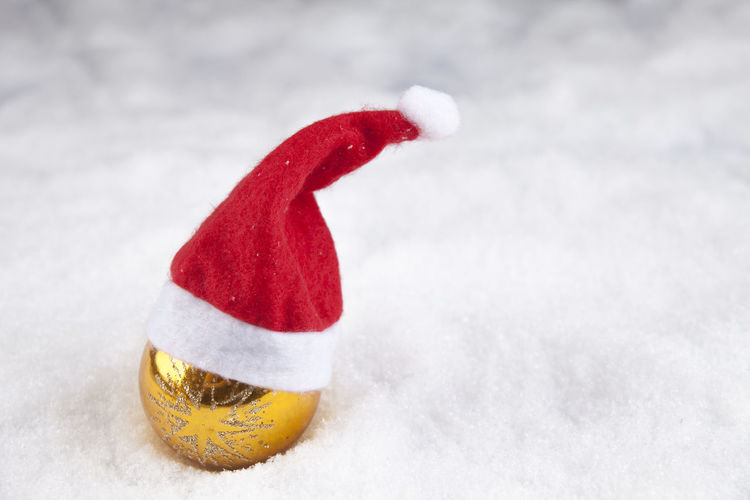 Close-up of bauble and santa hat on fur during christmas