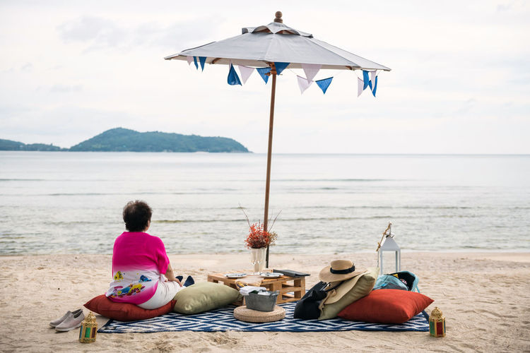 Old pension woman sit on beach picnic to drink, eat, and enjoy seascape view at beach in phuket