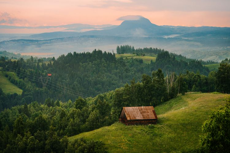 Scenic view of log cabin on field against mountain and sky at sunset