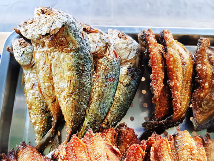 Fried mackerel and salted fish on stainless steel tray