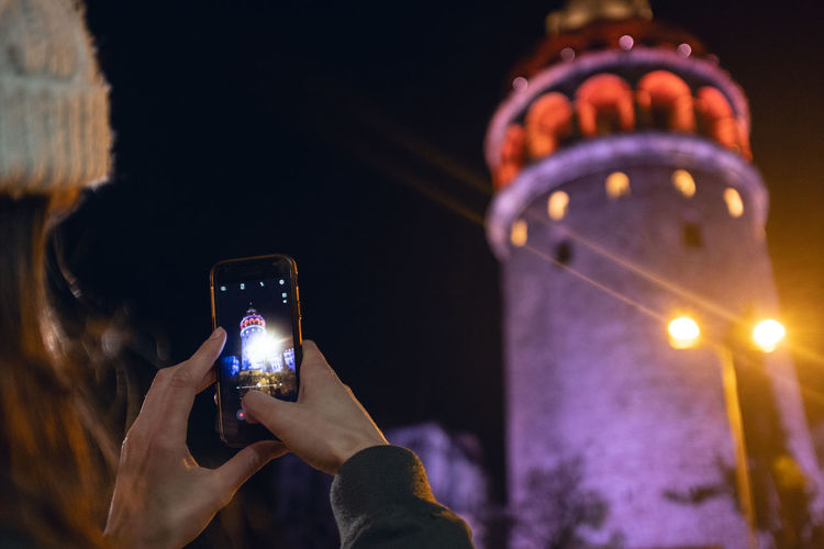 Galata Tower Technology Smart Phone Holding Photography Themes Photographing Mobile Phone Illuminated Activity Human Hand Wireless Technology Night Portable Information Device Hand Communication Focus On Foreground One Person Human Body Part Real People Connection Photo Messaging Outdoors Night Lights