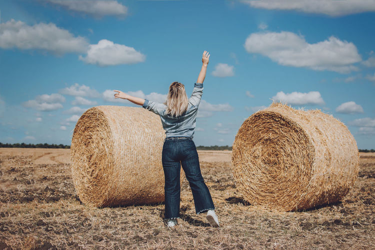 Full length of man with hay bales on field against sky