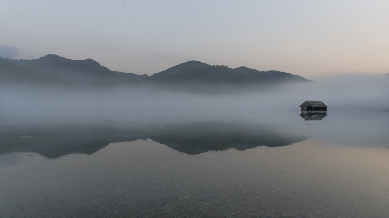 reflection, water, scenics - nature, beauty in nature, sky, tranquility, mountain, tranquil scene, fog, lake, waterfront, non-urban scene, no people, nature, idyllic, mountain range, standing water, copy space, outdoors, hazy
