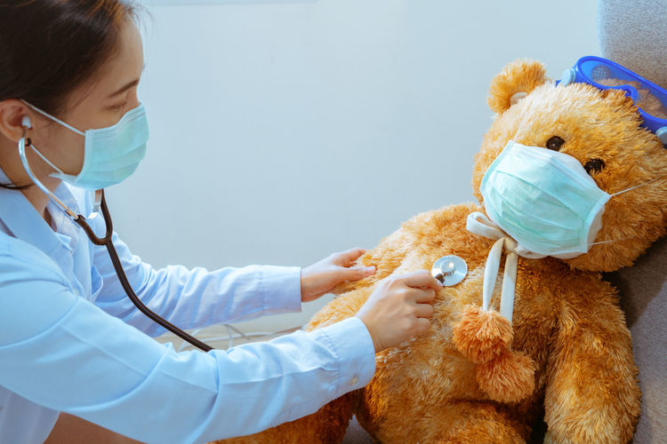 Side view of doctor examining stuffed toy