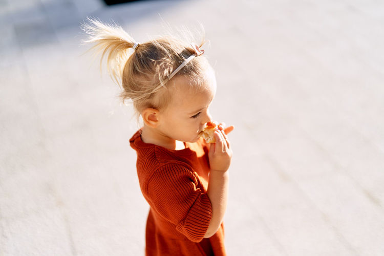 High angle view of girl eating food while standing outdoors