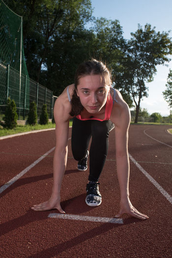 Portrait of young woman bending at track field