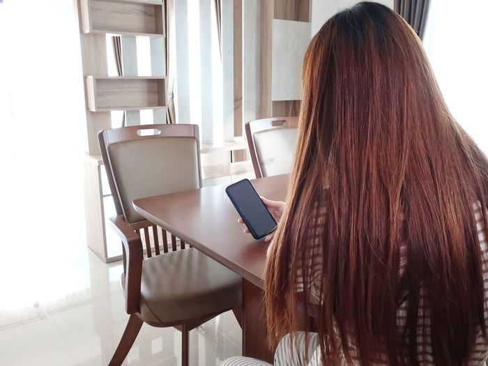 Rear view of woman using mobile phone at home
