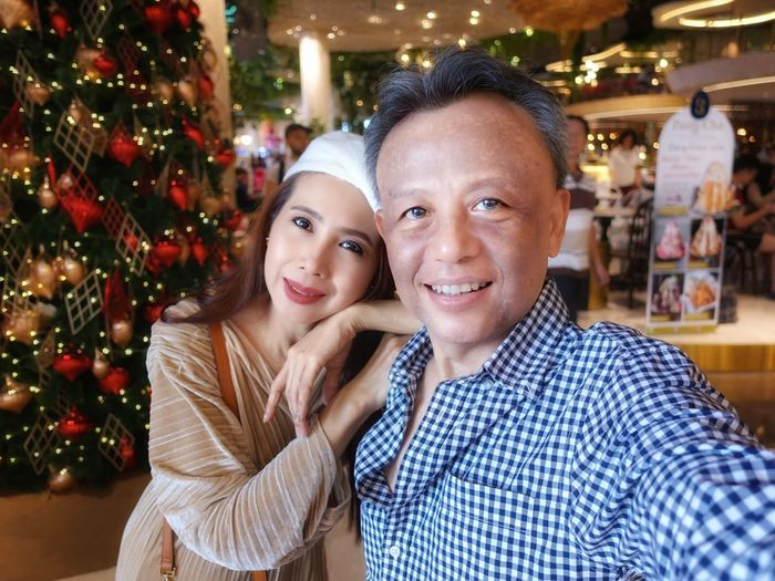 Portrait of smiling couple sitting in store during christmas
