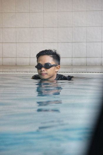 Portrait of young man swimming in pool