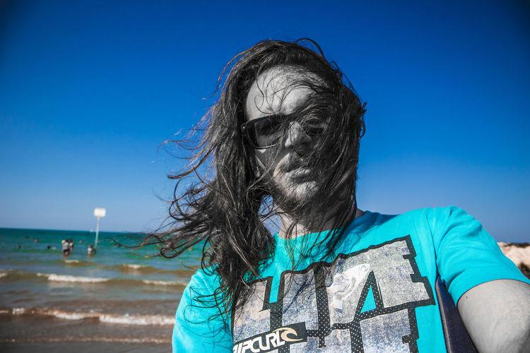 Portrait of man on beach against blue sky