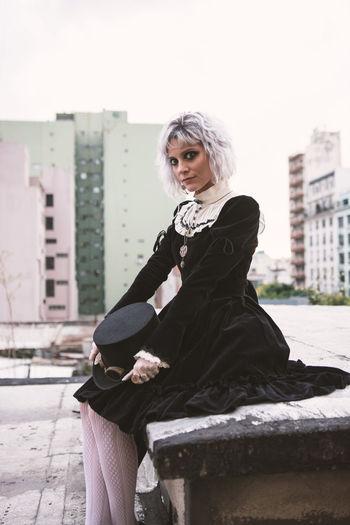 Portrait of woman sitting on city street