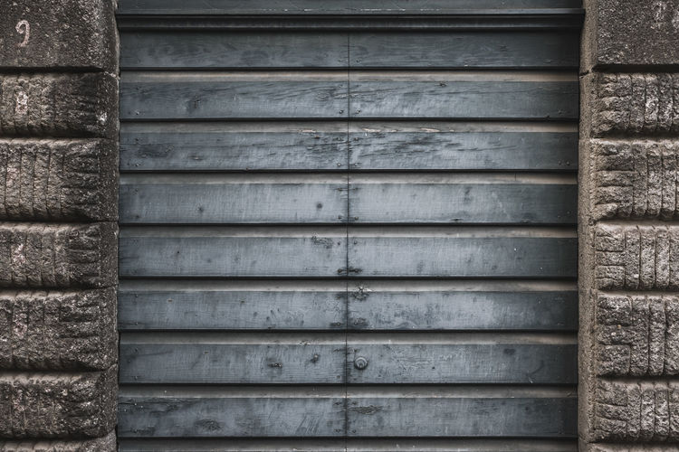 No People Backgrounds Wood - Material Architecture Pattern Metal Day Full Frame Textured  Wall - Building Feature Built Structure Close-up Closed Weathered Shutter Safety Old Security Protection Outdoors Iron Corrugated Garage Pattern, Texture, Shape And Form Pattern Pieces Patterns Door Doors Wall Stone Material Stone Wall Blue Grey Town Vintage Vintage Style Paint Europe Italy Italia Textured  Texture Textured Effect Background Background Photography Architectural Detail Gate