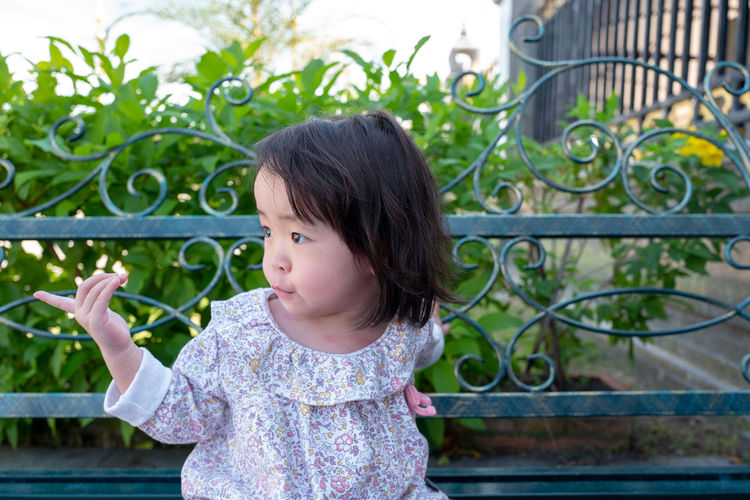 Childhood Child One Person Innocence Females Cute Looking Girls Women Casual Clothing Real People Day Railing Plant Standing Leisure Activity Barrier Fence Outdoors Hairstyle Bangs Contemplation