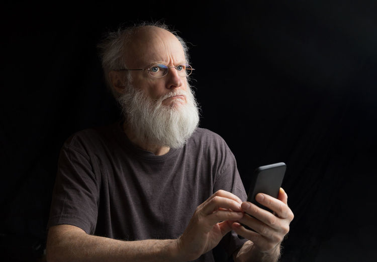 thoughtful senior man with smart phone One Person Wireless Technology Mobile Phone Beard Front View Connection Facial Hair Adult Holding Text Messaging Portrait Waist Up Communication Indoors  Males  Portable Information Device Smart Phone Technology Studio Shot Mature Adult Black Background Mature Men Thoughtful Confused Worried